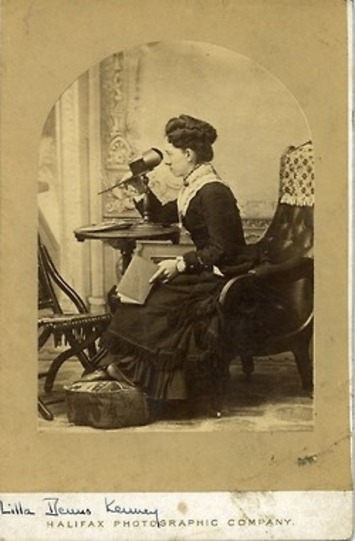 """Henrietta """"Lilla"""" Kenney seated with a stereograph viewer 