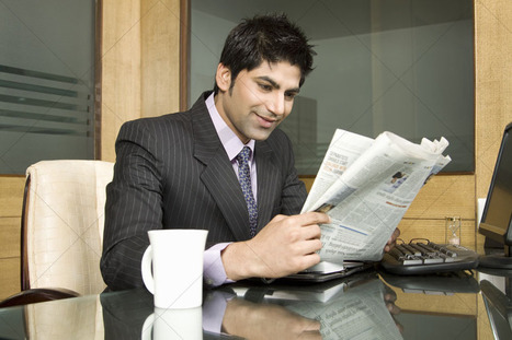 Mart Of Images-Low angle view of a young businessman reading newspaper. | Indian Images | Scoop.it