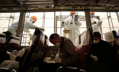 Workers carry out radiation screening on a bus during the media tour of the ... - The Guardian | GMOs & FOOD, WATER & SOIL MATTERS | Scoop.it
