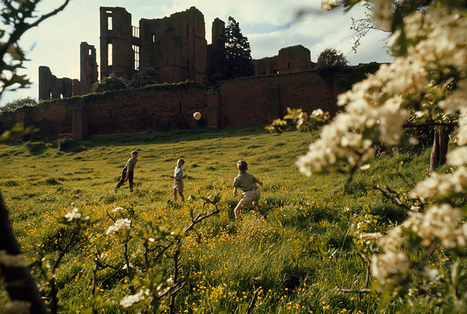 Young boys throw a ball on a lush green hillside below castle... | Interesting Photos | Scoop.it