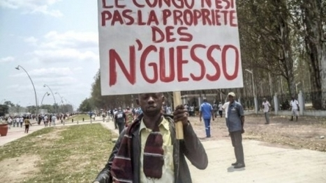 "A man holds a placard reading ""Congo is not the property of N'Guesso"" during an opposition demonstration in Brazzaville