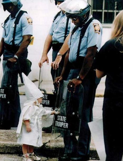 Un niño vestido con la indumentaria del KKK se acerca a un policía negro en Georgia, 1992 (by Todd Robertson) | Seguridad | Scoop.it