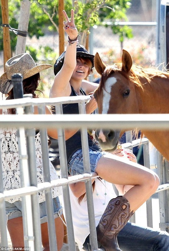 Go cowgirl! Paris Jackson is rodeo ready on mother Debbie Rowe's farm as she jumps on a fence clad in western boots and hat