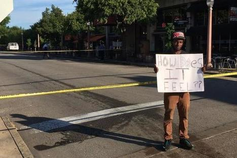 """How does it feel??"": Man holds sign at scene of shooting of a police officer 