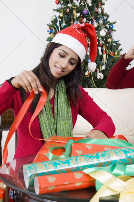 Mart Of Images-Front view of a young woman wrapping gifts of christmas. | Indian Images | Scoop.it