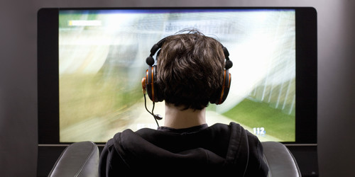Boy with headphones playing videogame on TV