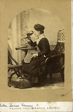 "Henrietta ""Lilla"" Kenney seated with a stereograph viewer 
