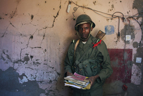 A Malian soldier holds papers next to a wall... | Photojournalism reporting | Scoop.it